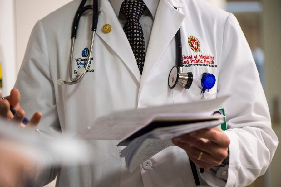 doctor in white coat with stethoscope and clipboard