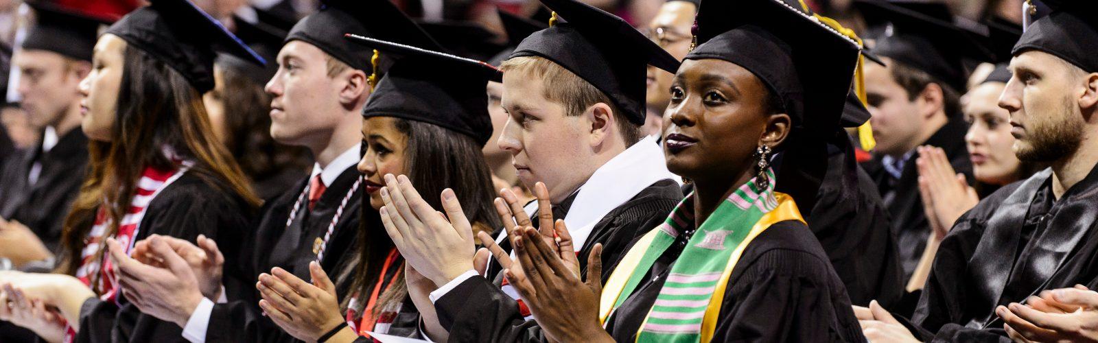 diverse graduates clap at commencement